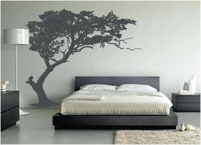 Спалнята с шикозно изрисувано дърво на стената създава домашно усещане.