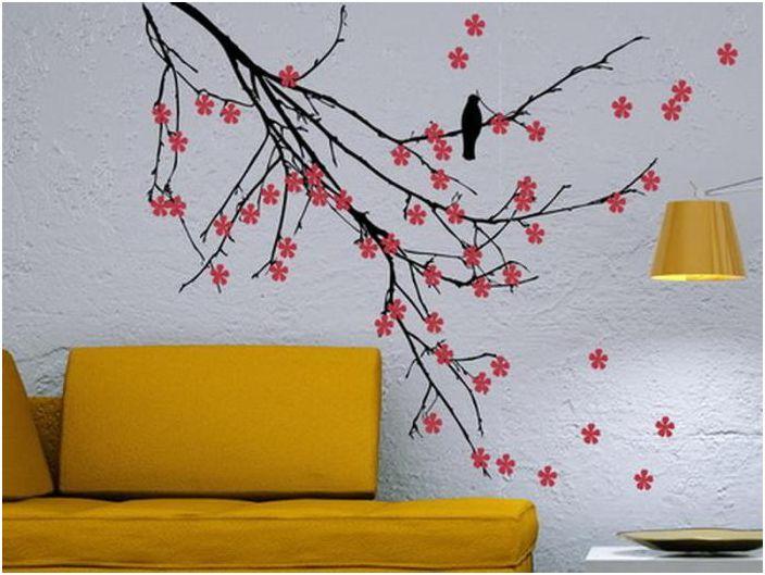 Стая с комбиниран интериор. Дърво с ярки цветове е нарисувано срещу сива стена, в допълнение към жълт диван.