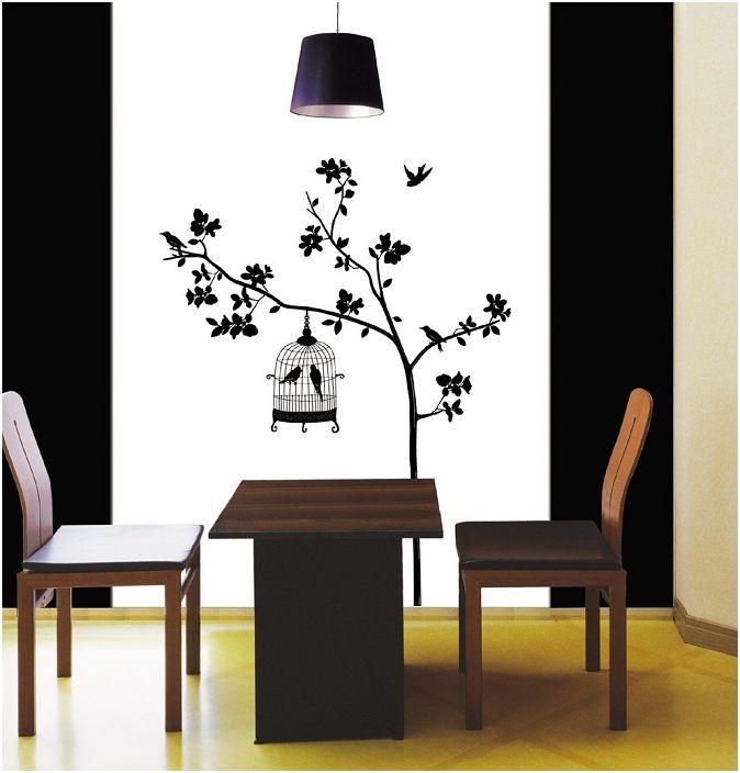 Черно-бялото изображение на дърво на стената особено стилно подчертава особеността на стаята и стила, в който е направена рисунката.