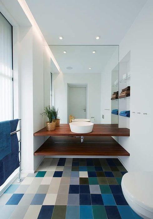 Pieni kylpyhuone näyttää suuremmalta peilatun seinän, valkoisten seinien ja aksentin vuoksi epätavallisessa lattiassa.