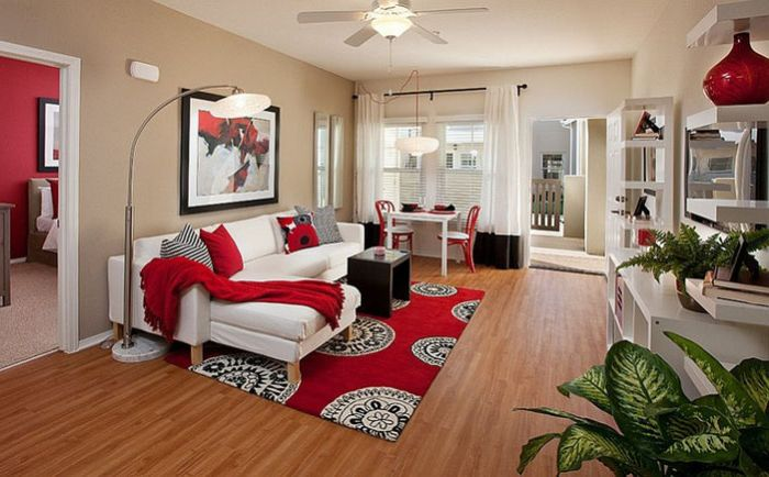 Living room with red accents by Borden Interiors & Associates