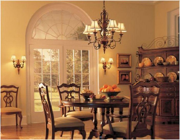 Une atmosphère chaleureuse dans une telle salle à manger est obtenue grâce à une combinaison réussie de couleurs et de matériaux à l'intérieur et d'un bel ajout au lustre.