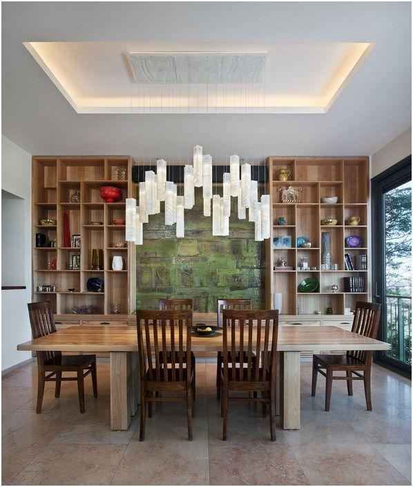 Множеството дървени елементи от интериора се допълват от красив полилей над масата.