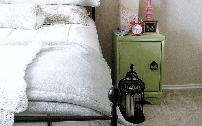Madárketrec gyertyával az ágy mellett