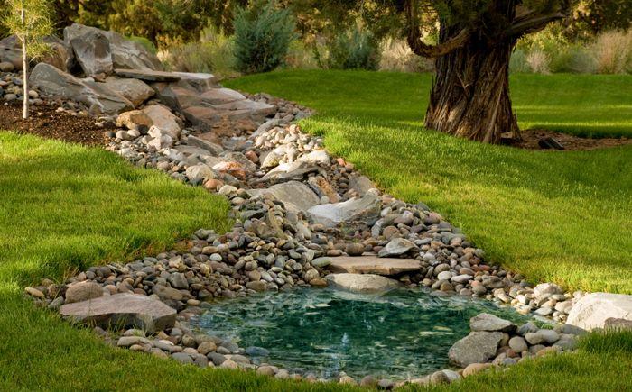 Малко езерце с малък фонтан. Гъстата трева и различни фигурки красят каменните брегове на резервоара.