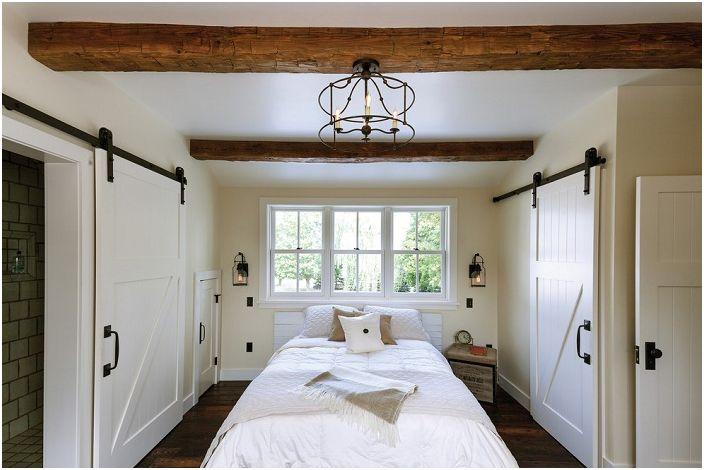 Снежнобялата спалня с разкошен прозорец и много врати хармонично се вписа в интериора на къщата.