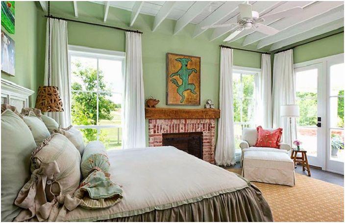 Уютна ментова зелена спалня с голямо легло и шикозни прозорци.