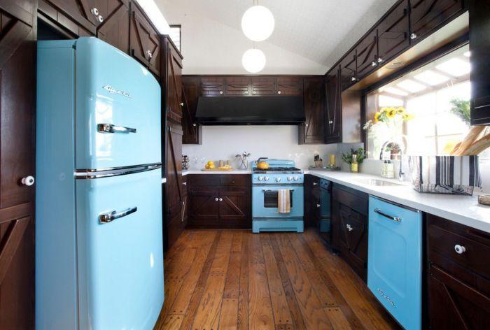 Тъмният кухненски интериор оживява с ярки и блестящи уреди.