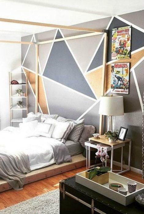 Sypialnia z geometrycznym nadrukiem na ścianie.