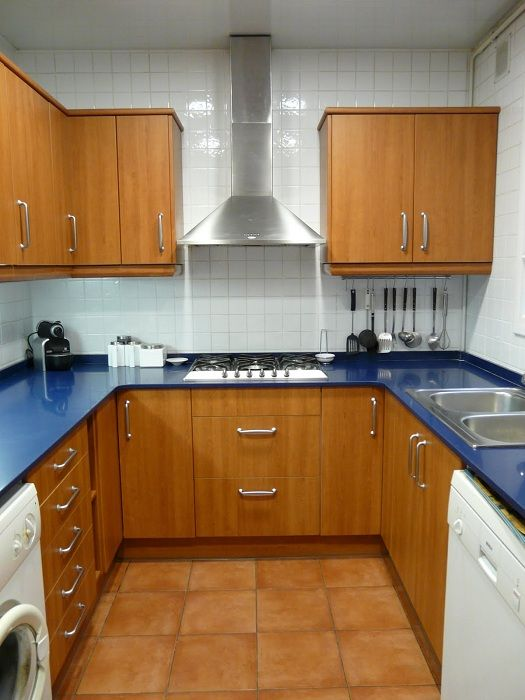 Кухня расположена на небольшой площади оформлена в дереве с отличными синими столешницами.