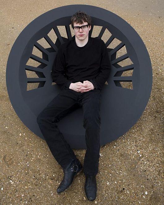 Молодой человек, сидящий на комфортном в кресле
