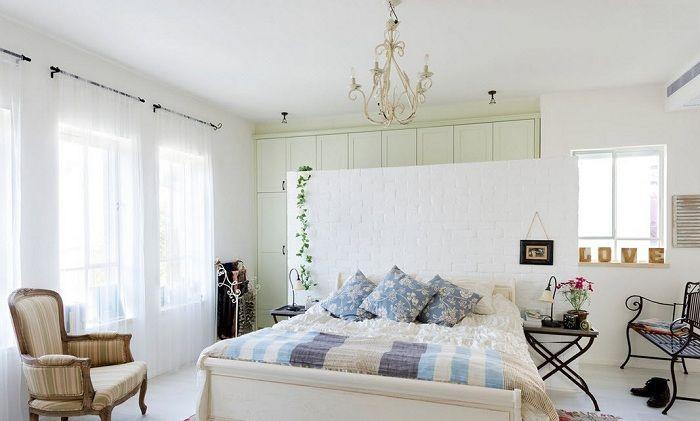 Традиционный светлый интерьер спальни разбавлен яркими акцентами цветочного текстиля и витой мебелью.