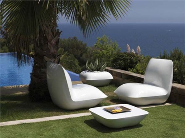Herlige lenestoler, bord og sokkel under et palmetre