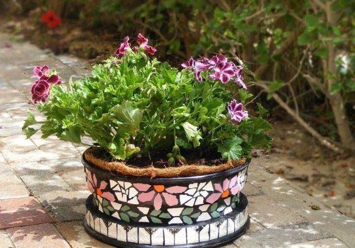 Цветы в горшке, декорированном плиткой, выглядят еще красивее.