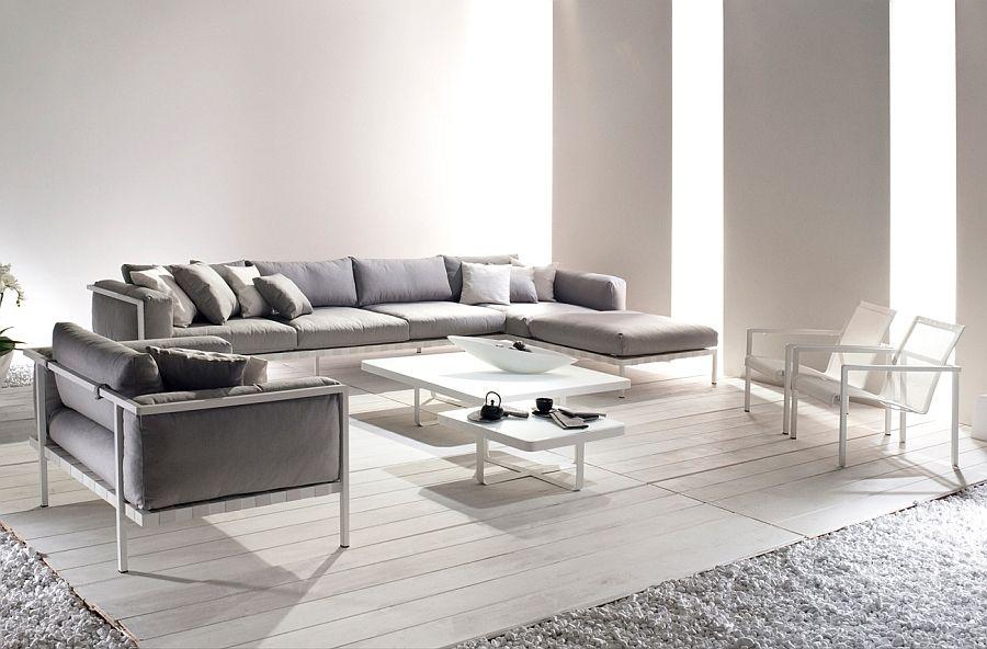 Polstret lenestol, sofa, stoler og bord i det indre av en lys stue