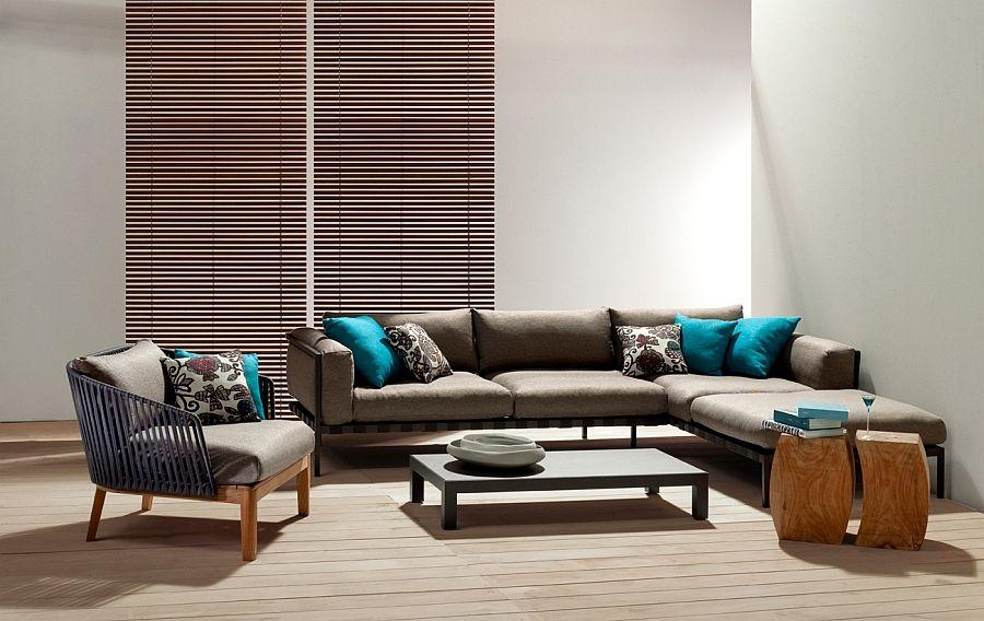 Диван с яркими подушками, кресло, стол и тумбы в интерьере гостиной