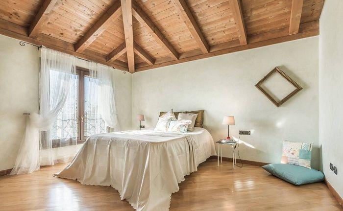 Оригинальный декор комнаты для сна с помощью деревянного потолка и милых белых штор.