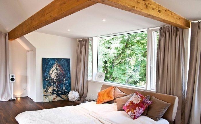 Удачный интерьер спальной с применением деревянных планок и шторами цвета кофе с молоком.