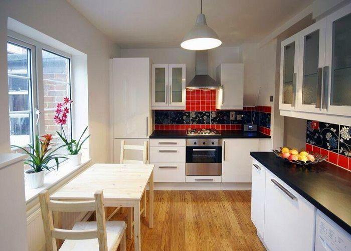 Viileä keittiö sisustus mustalla ja punaisella korostuksella.