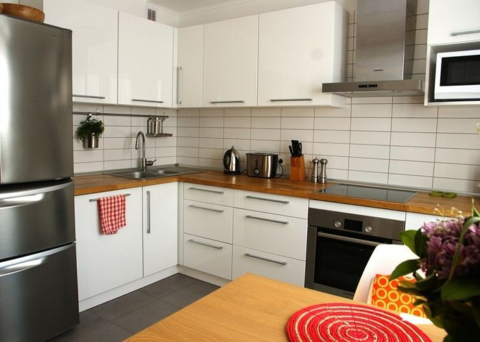 Кухненски интериор в светли цветове с дървен плот.