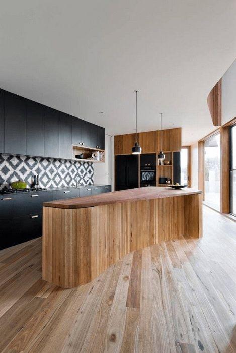 Зашеметяващ кухненски интериор, декориран в черно, който изглежда ефектно.