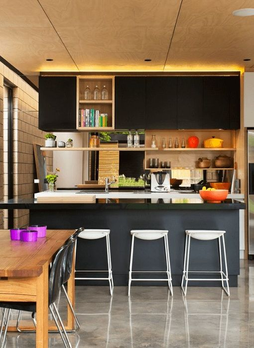 Готино дизайнерско решение за озаряване на кухнята в тъмни цветове със златисто осветление, което добавя цвят.