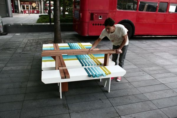 Мужчина собирает разноцветную скамейку