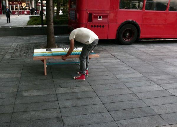 Мужчина собирает разноцветную чудесную скамейку