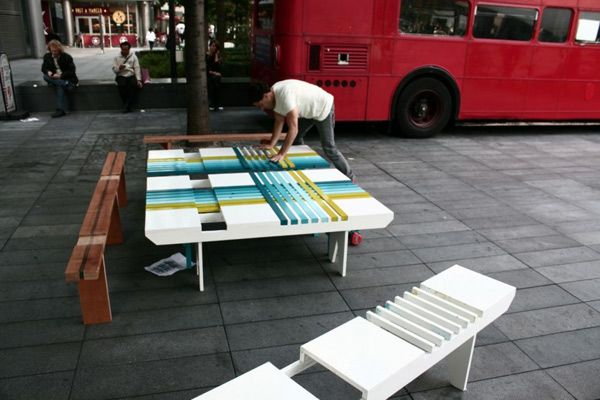 Мужчина собирает разноцветную креативную скамейку