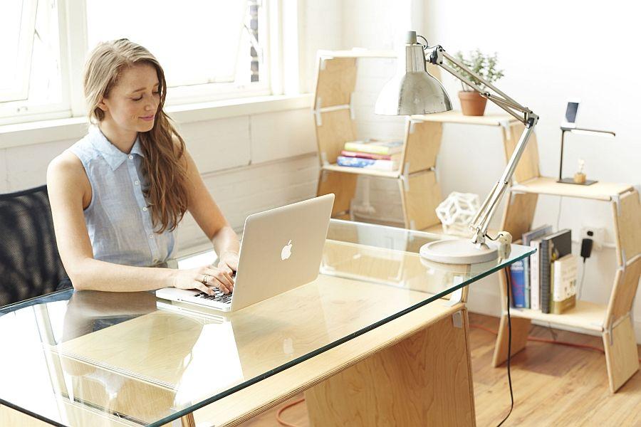 Stilig bord med glassplate, lampe og laptop på
