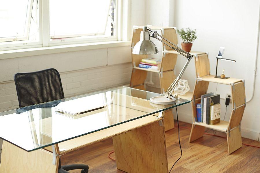 Kontorbord, lampe og modulære hyller ved vinduet