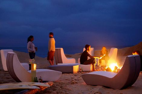 Les gens se détendre sur la plage avec des meubles pliants le soir