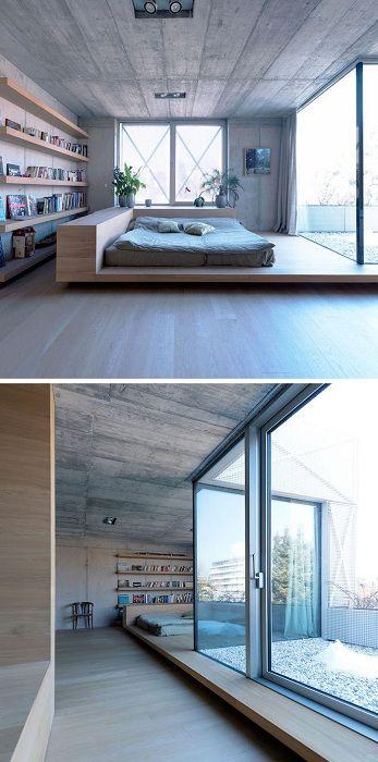 Oszałamiające wnętrze z fajnym łóżkiem na drewnianej platformie z eleganckim oknem.
