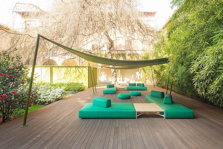 Зелен диван, тахти, дивани и дървена маса на терасата