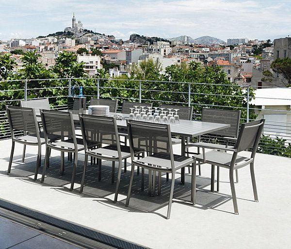 Harmaat tuolit pöydän ympärillä terassilla