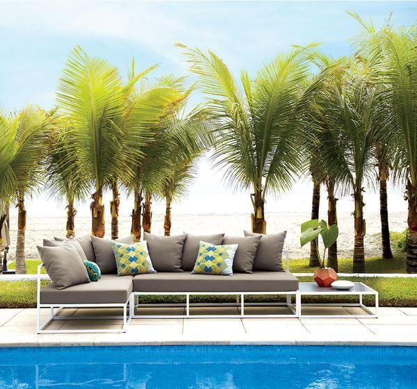 Un coin salon sous les palmiers au bord de la piscine