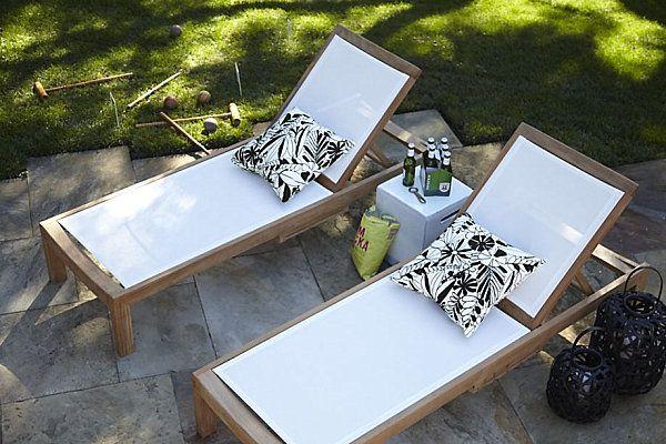 Oreillers noir et blanc sur des chaises longues en bois