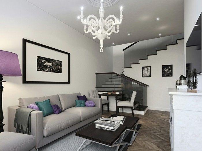 Дизайнът на хола в бели и сиви тонове е разреден с ярки декоративни елементи.