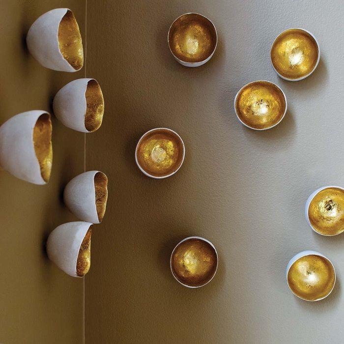 Fin transformasjon av veggen på grunn av interessant dekorasjon med gullfragmenter.