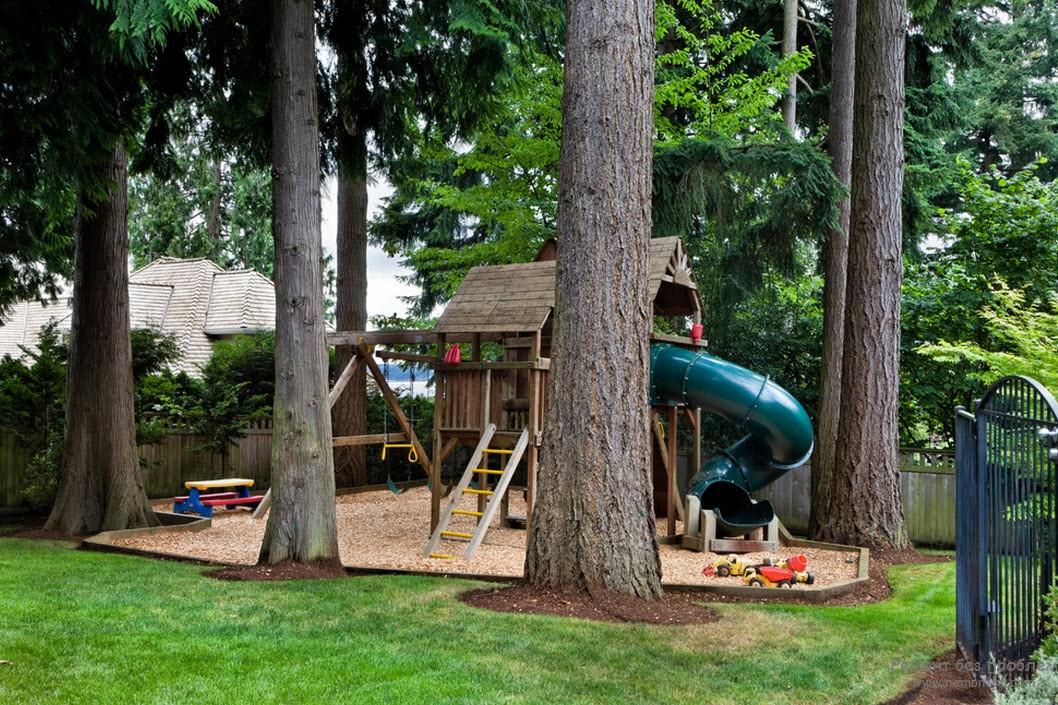 Деревянный детский домик на территории детской площадки